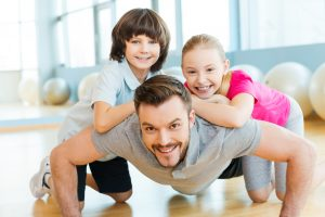 Happy little children bonding to their father doing push-ups in sports club