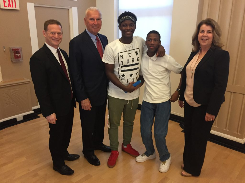 Attorney General Matt Denn, Mayor of Wilmington Mike Purzycki, TAKE ON SUMMER participants Kemuel Harding and his brother Kassel, and the Y of Delaware CEO Deborah Bagatta-Bowles, stop to pose for a photo after the press conference.